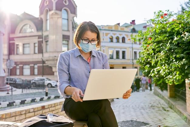 야외에서 작업하는 노트북과 얼굴 의료 보호 마스크에 성숙한 사업가. 도시 배경, 비즈니스 프리랜서, 건강 보호 개념