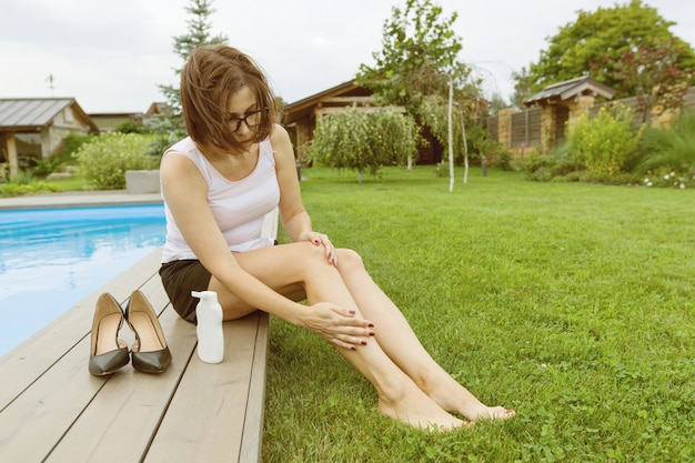 Mature businesswoman sits near the home pool.