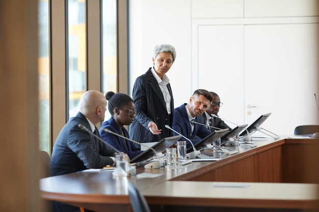 Зрелая деловая женщина, выступающая во время деловой конференции в зале заседаний