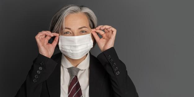 成熟した実業家は彼女の顔の保護マスクをまっすぐにします。ポジティブな女性がカメラに微笑む。切る