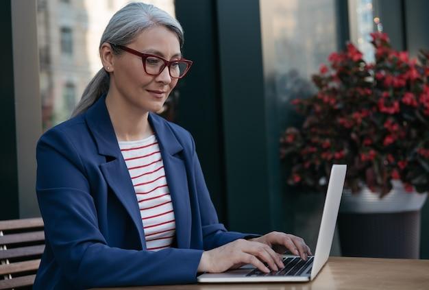 Зрелая деловая женщина, использующая портативный компьютер, работающая в интернете