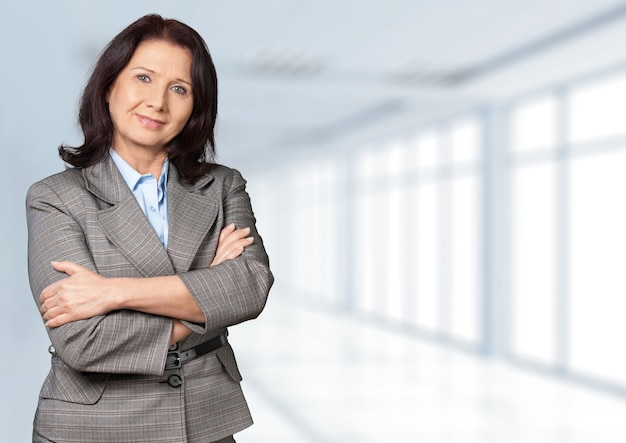 Mature businesswoman wearing formal suit on background