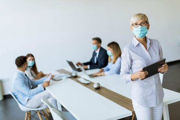 Зрелая коммерсантка с защитной маской используя цифровую таблетку в офисе