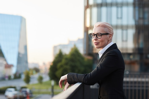 Mature businesswoman with short hair in black suit looking at view of the city while standing on balcony