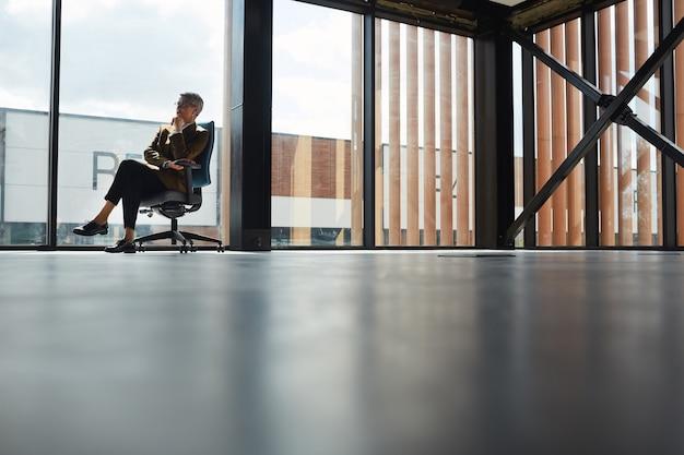 オフィスの大きな窓に椅子に座って新しいビジネスのアイデアを考えている短い髪の成熟した実業家