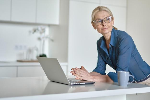 ラップトップコンピューターを使用して電子メールをチェックし、コーヒーを飲みながら自宅で働く成熟した実業家