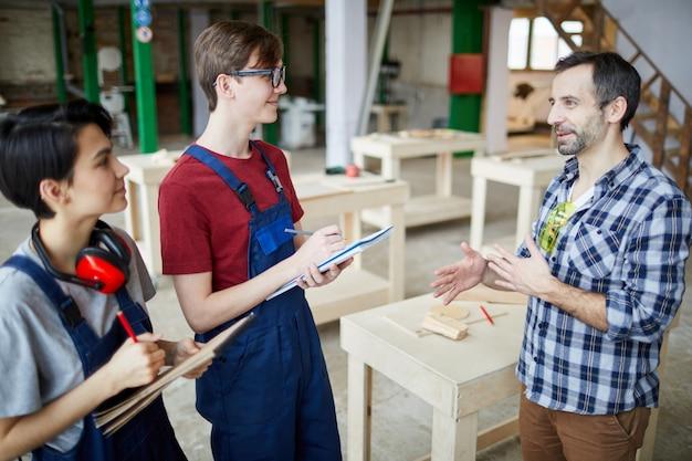 Mature carpenter instructing trainees