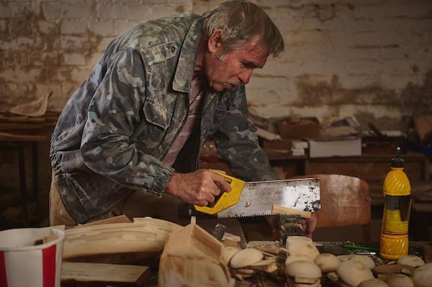 Зрелый плотник распиливает дерево пилой в своей мастерской для изготовления деревянных игрушек. изготовление поделок из дерева своими руками