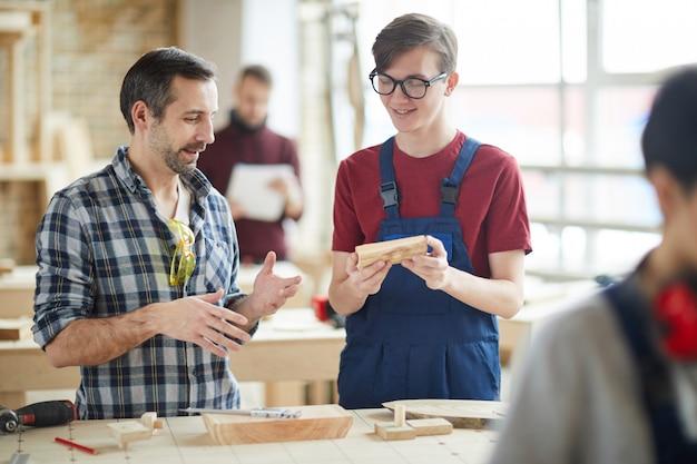 Mature carpenter talking to apprentice