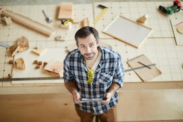Mature carpenter using digital tablet
