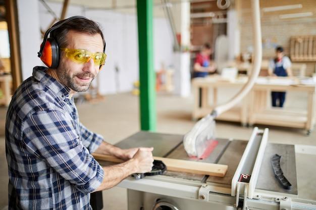 Зрелый плотник, используя машины в мастерской