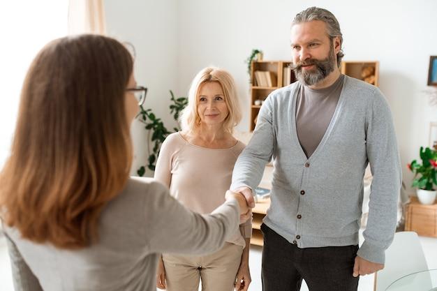 Зрелая случайная пара приветствует своего консультанта по недвижимости в офисе, собираясь искать новую квартиру или дом