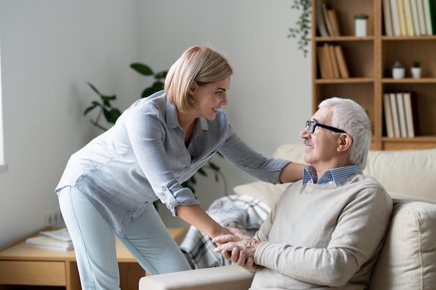 家庭環境でのチャット中に彼女を見ながら彼の娘の手を握ってソファの上の成熟したカジュアルな男