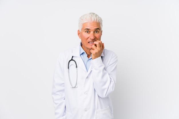 Mature caucasian doctor man biting fingernails, nervous and very anxious.