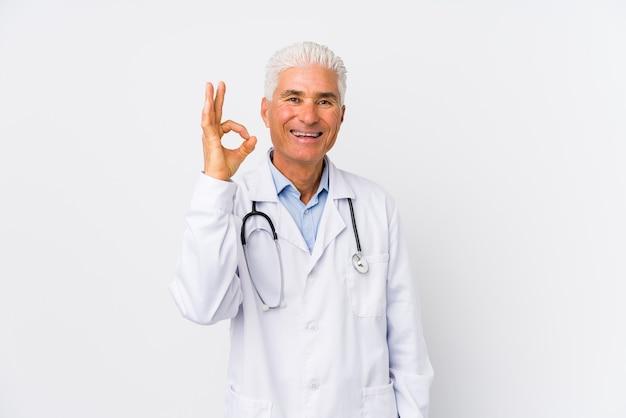 Зрелый кавказский человек доктора веселый и уверенный, показывая одобренный жест.