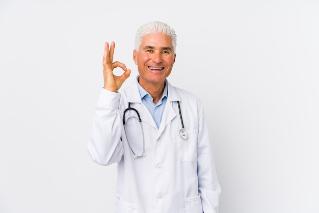 Mature caucasian doctor man cheerful and confident showing ok gesture.