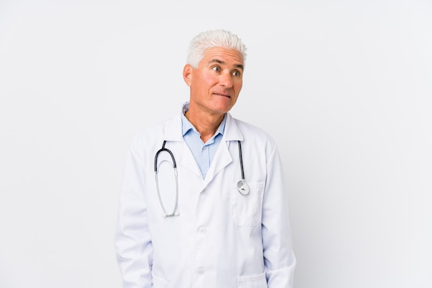 Mature caucasian doctor man confused, feels doubtful and unsure.