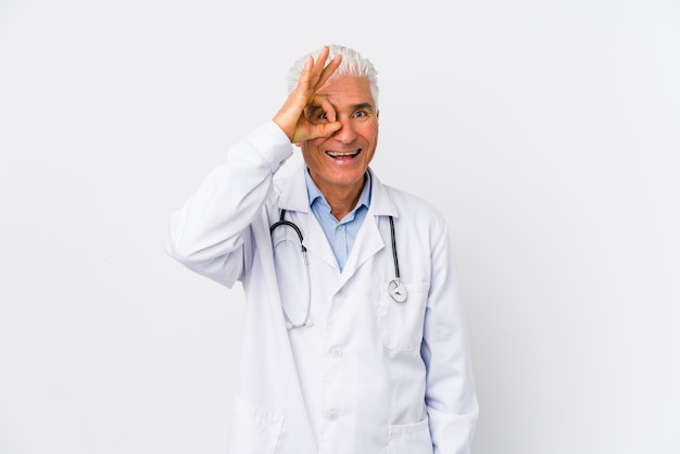 Mature caucasian doctor man excited keeping ok gesture on eye.