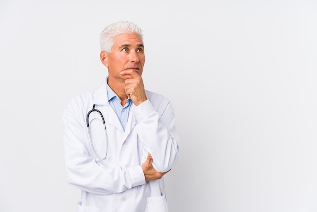 Mature caucasian doctor man looking sideways with doubtful and skeptical expression.