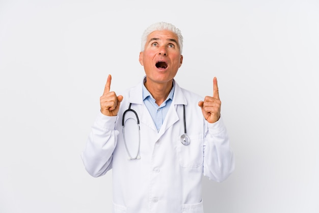 Mature caucasian doctor man pointing upside with opened mouth.