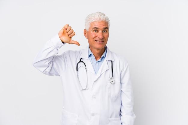 Зрелый кавказский человек доктора показывает жест неприязни, большие пальцы руки вниз. концепция несогласия.