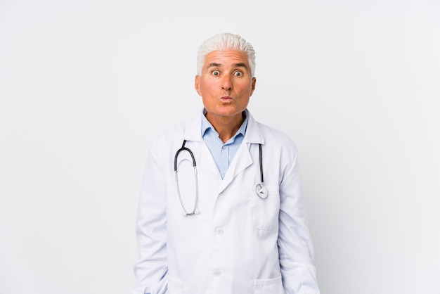 Mature caucasian doctor man shrugs shoulders and open eyes confused.