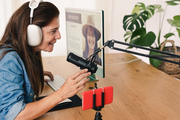 Mature caucasian influencer woman recording audio and streaming live video online with smartphone