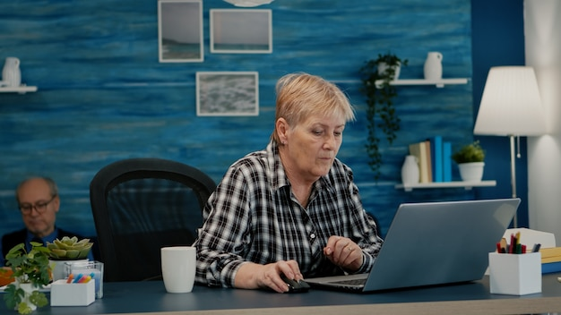 Mature caucasian lady working on laptop at home workplace, typing on computer drinking coffee. experienced manager doing financial project during self isolation while husband reading a book in backgro