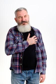 Зрелый кавказский мужчина, одетый в повседневную одежду, чувствует себя плохо, держа руку на груди с болью в сердце, белая стена