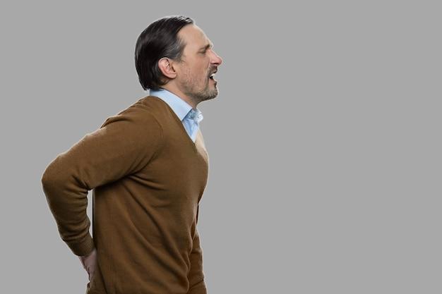 끔찍한 요통 데 성숙한 백인 남자입니다. 회색 배경에 허리 통증으로 고통받는 중년 남성을 강조했습니다.