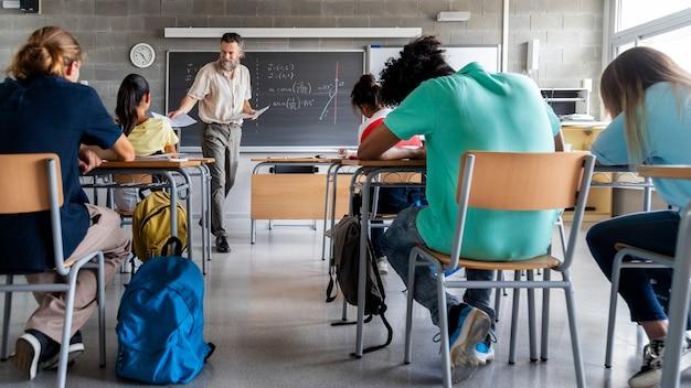 Зрелый кавказский учитель вручает экзамены многонациональным старшеклассникам. студенты готовы к экзамену. горизонтальный фото-баннер