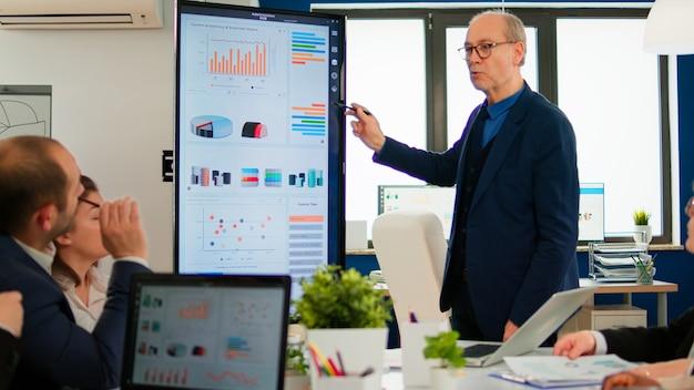 통계 데이터, 재무 프로젝트 브리핑 다양한 직원 그룹을 제시하는 성숙한 ceo cto 전무이사. 회의 모임 중 전문 스타트업 회사에서 일하는 다민족 팀