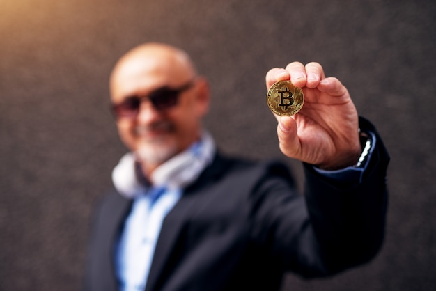 Mature cheerful businessman is extending arm showing a bitcoin to the camera.