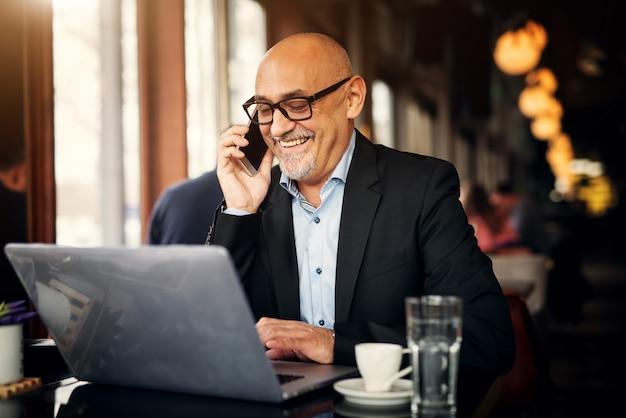 成熟した陽気なビジネスマンが電話をかけ、コーヒーショップのテーブルに座って笑っている間ノートパソコンを使用しています。