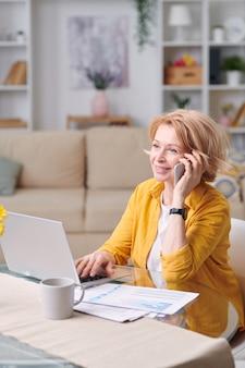 Зрелая жизнерадостная бизнес-леди со светлыми волосами разговаривает с кем-то на смартфоне, работая удаленно дома во время карантина