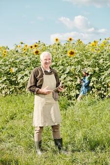 화창한 날 해바라기 밭과 여성에 대해 터치패드를 사용하여 카메라 앞에 서서 작업복을 입은 성숙한 쾌활한 남성 농부