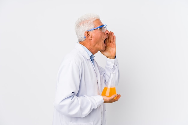Mature chemical man isolated shouting and holding palm near opened mouth.