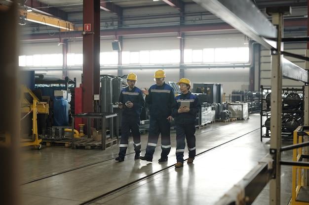 안전모를 쓴 성숙한 수석 엔지니어는 산업 상점을 따라 걷고 젊은 노동자들에게 작업을 제공하는 동안 손짓을 합니다.