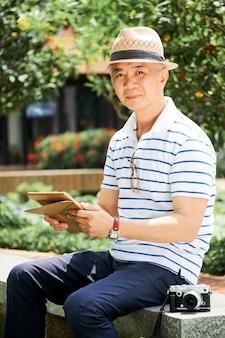 Зрелый китаец отдыхает в парке