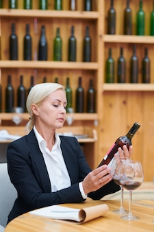 Mature confident winery expert sitting by table in cellar of restaurant while looking at bottle of red wine