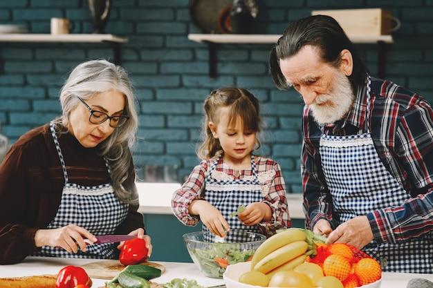 成熟したカップルとその孫娘が食事を準備している