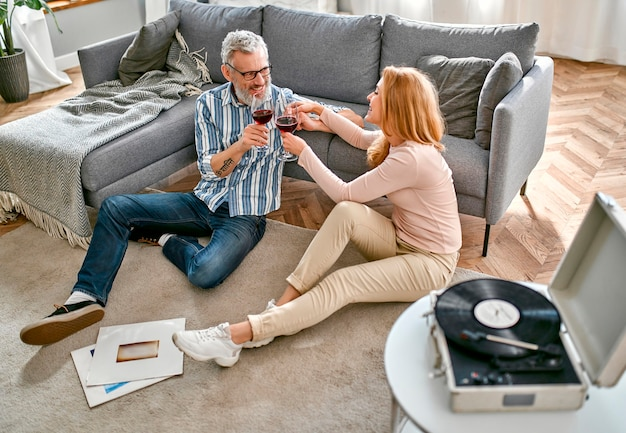 A mature couple are sitting on the floor near the sofa with glasses of wine, relaxing, enjoying life at home and listening to vinyl records
