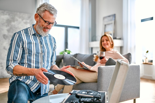 Mature couple are sitting at home on the couch, relaxing, enjoying life, drinking wine and listening to vinyl records on a music player.