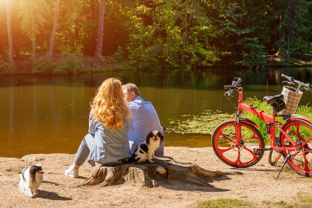 Пожилая пара на берегу озера с собакой и велосипедом, сидя на солнце