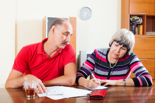 Mature couple calculating family budget