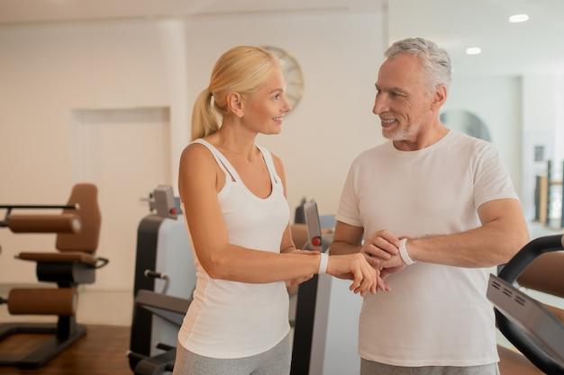 Пожилая пара проверяет пульсометры в тренажерном зале и выглядит позитивно