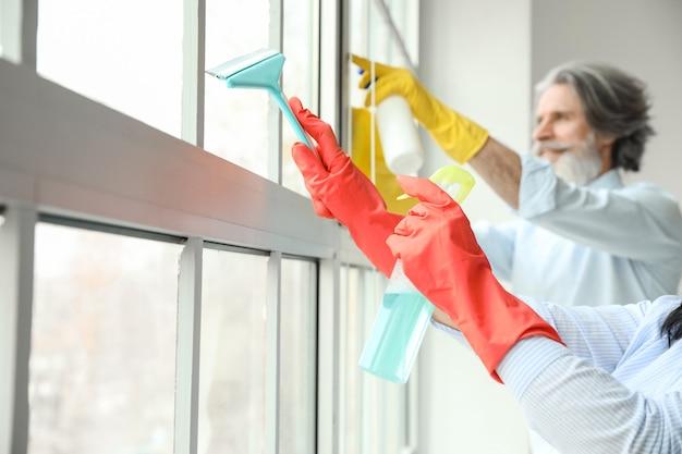 그들의 아파트에서 창을 청소하는 성숙한 부부