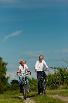 Mature couple cycling on rural road in summer