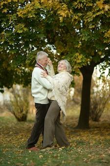 Пожилая пара танцует в осеннем парке