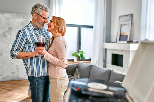Mature couple dancing with glasses of wine, relaxing, enjoying life at home and listening to vinyl records on a music player